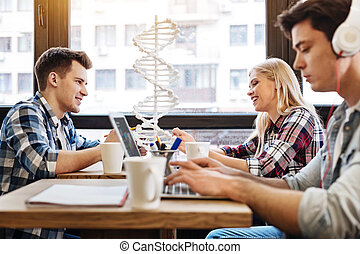 Cheerful students sitting together in the cafe