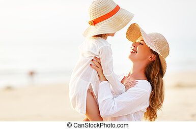 happy family at beach. mother and child daughter hug at sunset