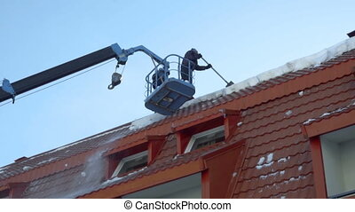 Worker removing snow on the roof of the building - Worker on...