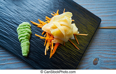 Ginger and Wasabi on a carrots bed and black slate board