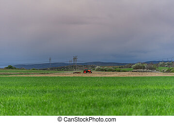 Farmer with tractor seeding crops at field