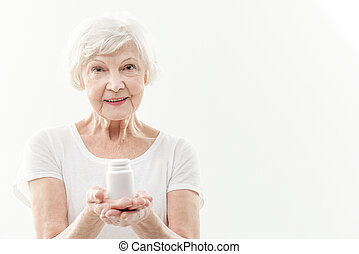 Happy old lady advising to take pills - Waist up portrait of...