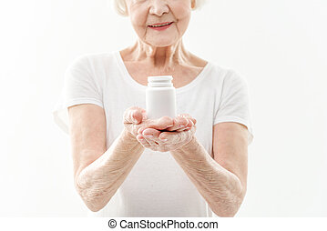 Cheerful mature woman presenting vitamins - Kind old lady is...