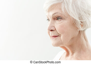 Wrinkled old woman thinking about life - Pensive mature lady...