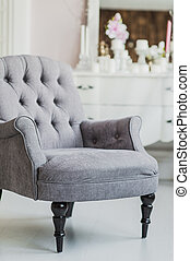 beige color upholstered chair in living room with flowers