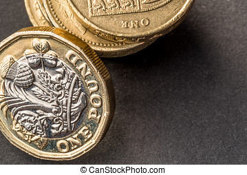 New british one sterling pound coin on dark background.