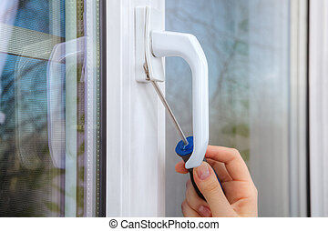 Removing handle of a plastic window using hand screwdriver.