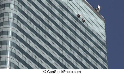 London. Window washers on the wall of a skyscraper. -...