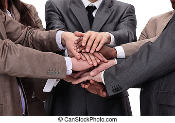 Group of business people putting their hands on top of each...