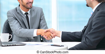 Two business people shaking hands with each other in the office