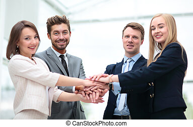 Close up top view of business people putting their hands...