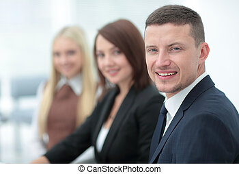 Elegant co-workers looking at camera during meeting in...