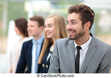 Business people standing in a row looking in same direction