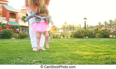 Baby girl doing first steps with mothers help - Little cute...