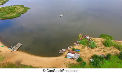 Aerial view of motorboat coming into lake cove - Aerial view...