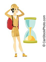 Worried asian traveler woman looking at hourglass.