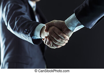concept of partnership in business: a handshake of business partners.