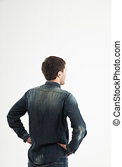 rear view of a stylish young man looking forward to the empty sp