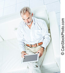successful businessman with digital tablet sitting in modern office chair.