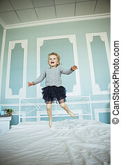 happy five year old girl jumping on the bed in the parents '...