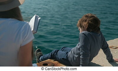 Mom reads book to son, nature scenery next to sea outdoors