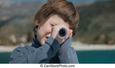 The boy holds the twisted sheet as a telescope and looks...