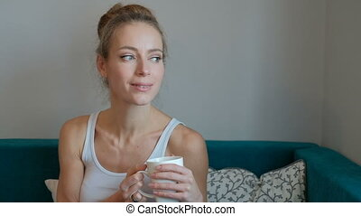 A woman in a white shirt holding a cup and looking at with...