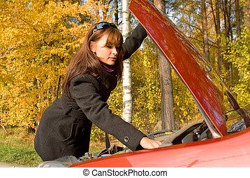 The girl repairs the car motor