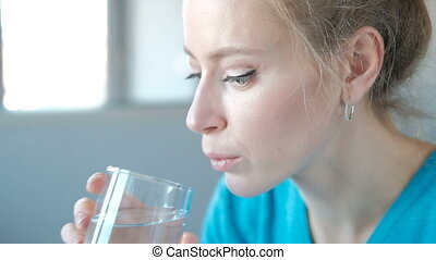 Close-up shooting of a woman face taking pills drinking...