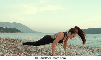 Young slim woman in training suit do exercises on beach near ocean.