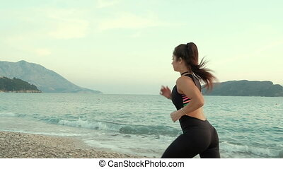 Young slim woman in training suit running along beach near sea.