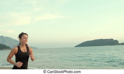 Sporty woman running on sea shore beach in the morning....