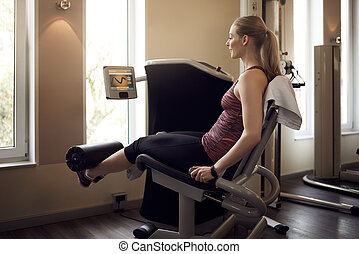Smiling woman using weight machine in gym for legs, viewed...