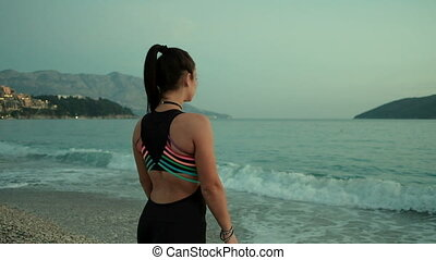 woman walking on sea shore mountains on background, looking