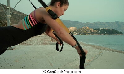 Athlete woman doing exercises with tight band fitness...
