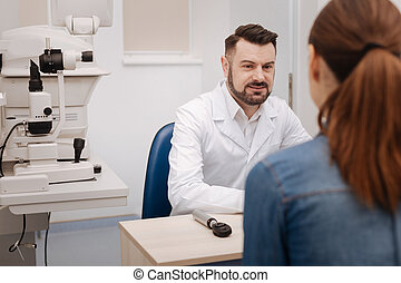 Handsome pleasant ophthalmologist sitting at the table
