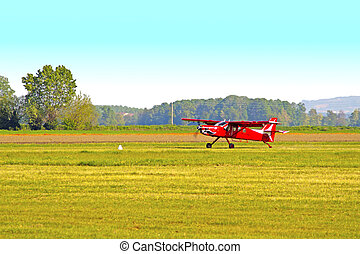 Plane - Old red plane rolling over a track in the fields
