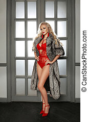 Beautiful alluring sexy woman portrait in red fashion lingerie and shoes heels wears sable fur coat posing by modern door with frame in luxury interior.