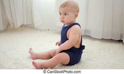 little baby boy of five months, crawling on the floor in the...