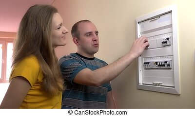 couple check circuit breaker electricity in own home. -...