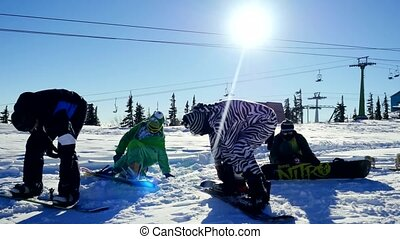 Group of young snowboarders on the slopes in sunny winter...