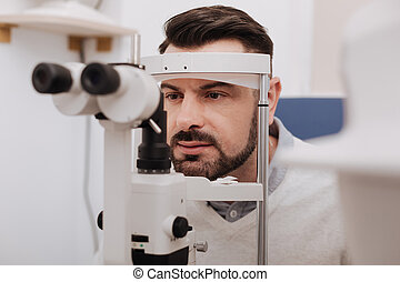 Serious handsome patient having his vision tested