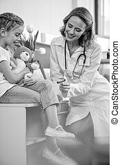 side view of smiling doctor examining girl with reflex hammer, black and white photo