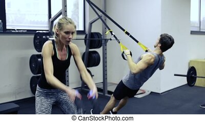 Young people in crossfit gym working out with various...