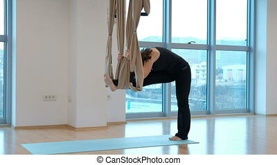 In yoga in the air, a woman makes a hammock grip with one...