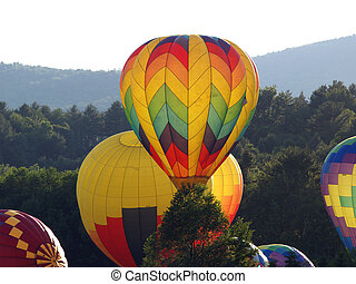 Hot Air Balloons launch over scenic Stowe, Vermont at the...