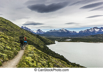 two men hiking in patagonia mountains, torres del paine with grey sky