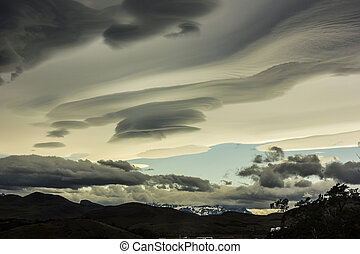 lenticular clouds above snowy mountains in Patagonia - grey...
