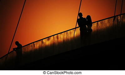 Lovers Couple At Dusk On Bridge Back Lit Silhouette. -...