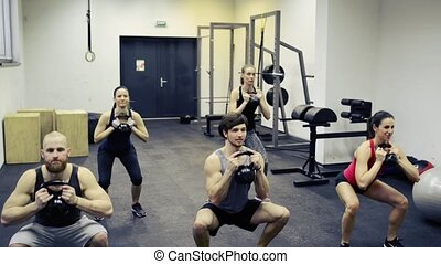Young people in crossfit gym doing squats with kettlebells -...